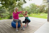 Front view of beautiful Caucasian female trainer assisting active senior Caucasian woman to exercise poster