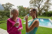 Side view of beautiful Caucasian female trainer and active senior Caucasian woman drinking water in  poster