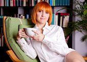 Frau mit roten Haaren ist auf einem Stuhl sitzen und Kaffee trinken