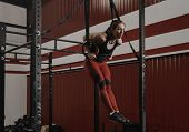 Young Woman Doing Muscle-ups On Gymnastic Rings At The Gym. Strong Female Athlete Doing Ring Dips Wh poster