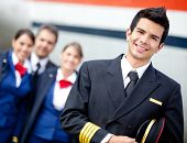 stock photo of work crew  - Captain pilot with cabin crew and an airplane at the background - JPG