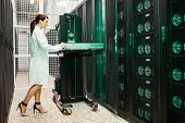 Serious Attractive Young Woman In Lab Coat Inserting Hardware Into Supercomputer While Working In St poster
