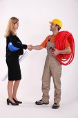 Business professional shaking a tradesman's hand