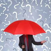 Businessman holding red umbrella with question mark rain concept for confusion, decisions or busines