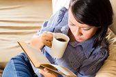 Schüler - junge asiatische Frau oder ein Mädchen sitzen auf einem Sofa mit einer Tasse Kaffee ein Buch zu lesen, sie ist le