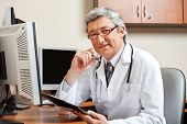 Portrait of mature male doctor with clipboard sitting in front of computer at clinic