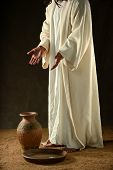 Jesus standing with hands extended and pointing to a jar and bowl