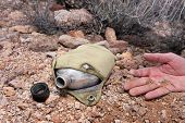 stock photo of canteen  - A hiker in the extreme wilderness succumbs to dehydration while in the remote desert - JPG