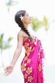 Beach woman on Hawaii relaxing enjoying the sun in serene relaxed pose. Hawaiian scene with beautifu