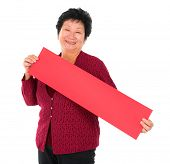 Chinese senior woman with red spring couplets standing over white background