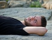 Attractive Young Man Lying On His Back On A Rock, Looking In Camera
