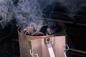 stock photo of briquette  - Flaming hot charcoal briquettes in a grill starter - JPG