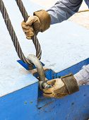 stock photo of shackles  - Close up worker fitting bolt anchor shackle with wire rope sling on crane counter weight - JPG