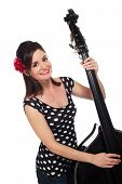 foto of rockabilly  - A Beautiful Rockabilly Girl Smiling and Playing a Black Double Bass - JPG