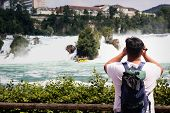 Tourists Take Pictures Of The Rhine Falls In Switzerland