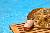 Suntan Lotion And Straw Hat By The Pool poster