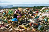 People pick up refuse at rubbish dump