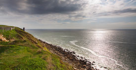 picture of wooden fence  - Looking out over a shiny silver sea under impressive clouds - JPG