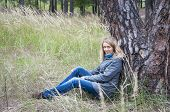 Girl Sitting In Tall Grass Near A Pine Tree.