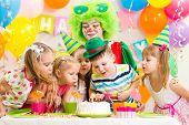 stock photo of birthday hat  - kids with clown celebrating birthday party and blowing candle on cake - JPG