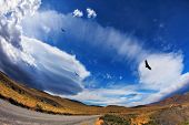Journey into a far country. Gravel road, incredible forms clouds and Andean condors. The picture was