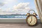 stock photo of under sea  - View of summer sea under blue sky from window with alarm clock - JPG