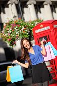 London shopping woman happy excited holding shopping bags by red phone booth. Female shopper smiling in London, England, United Kingdom during spring or summer. Multicultural Asian Caucasian model.