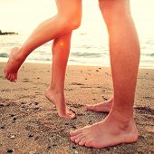 Kissing lovers - couple on beach love concept showing feet in close up. Woman standing on toes to kiss man at sunset during romantic summer holidays vacation.