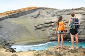Hikers - travel couple tourists hiking on Hawaii. Tourist backpackers walking on Green Sand Beach, P