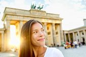 Berlin people - woman at Brandenburg Gate or Brandenburger Tor, smiling happy in Berlin, Germany. Be
