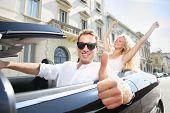 Car driver happy giving thumbs up - driving couple excited on road trip travel vacation. Male driver
