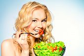 stock photo of cook eating  - Portrait of a beautiful young woman eating vegetable salad - JPG