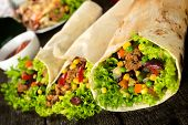 stock photo of sandwich wrap  - Beef and vegetables in tortilla wrap sandwich.Selective focus on the front sandwich