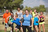 stock photo of boot camp  - Smilng woman and boot camp fitness group with medicine ball