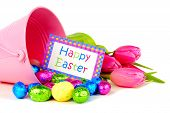 stock photo of easter candy  - Happy Easter card in a pail with spilling candy and tulips over white - JPG