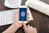 stock photo of fingerprint  - female hands holding a white touch phone over the desk in the office and entering the PIN code of fingerprint - JPG