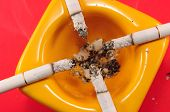 yellow ashtray with a burning cigarette on red