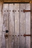 old wooden door with rusty hinges metal rivets