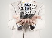 Businessman Hand Showing Design Word Thinking Outside Of The Box As Concept