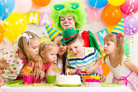 picture of clowns  - kids with clown celebrating birthday party and blowing candle on cake - JPG