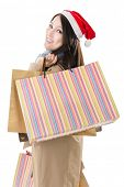Happy shopping girl holding bags and wearing Christmas hat, half length closeup portrait on white ba