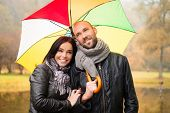 Happy middle-aged couple with umbrella outdoors on beautiful rainy autumn day