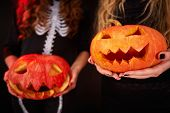 Photo of carved Halloween pumpkins held by females