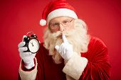 Santa Claus holding clock showing five minutes to midnight and making shhh gesture