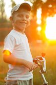 Funny Smiling Boy With Bike At The Summer Park In Beam Of Sunset