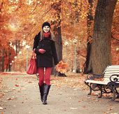 Young and beautiful girl walking in bright and colorful autumn park
