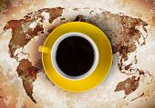 Close up of cup of coffee and world map at background