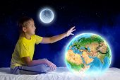 Cute boy sitting in bed and dreaming. Elements of this image are furnished by NASA