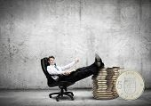 Young confident businessman sitting in chair with legs on stack of coins
