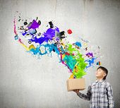 Young boy splashing colorful paint from carton box